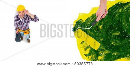 Handyman holding paint roller against blue and yellow paint making green