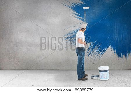 Man using paint roller on white background against grey room