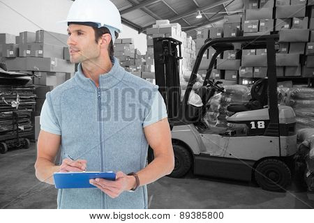 Architect writing on clip board against warehouse worker loading up pallet