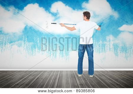 Man using paint roller on white background against painted sky