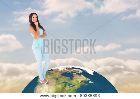 Casual brunette smiling at camera against beautiful blue sky with clouds