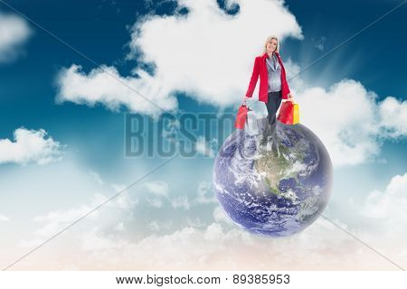 Happy blonde in winter clothes holding shopping bags against blue sky