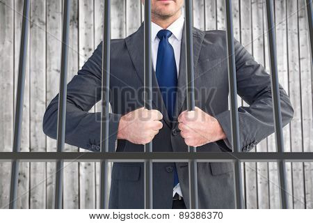 Businessman holding his hands out against digitally generated grey wooden planks