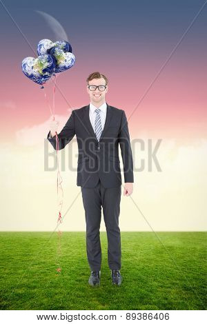 Happy geeky hipster businessman holding balloons against magical sky