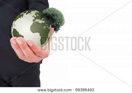 Businessman holding out his hand against tree with green leaves growing