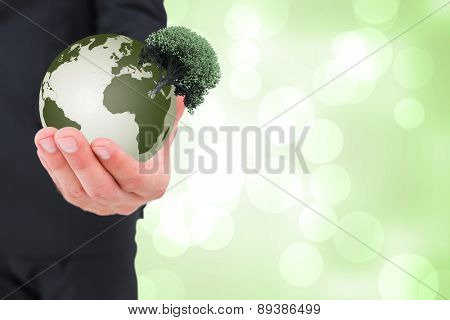 Businessman holding out his hand against green abstract light spot design