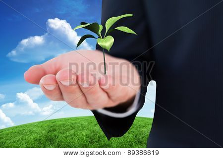 Mid section of a businessman with hands out against green hill under blue sky
