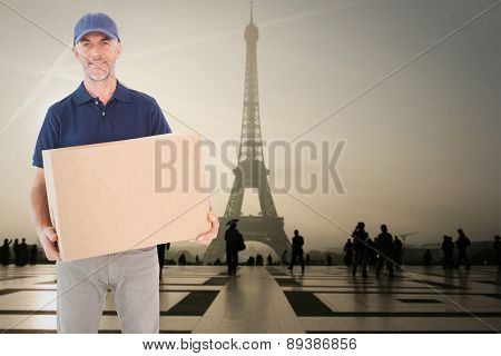 Happy delivery man holding cardboard box against eiffel tower