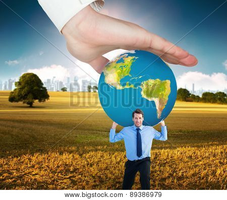 Hand presenting against field with tree and city on the horizon
