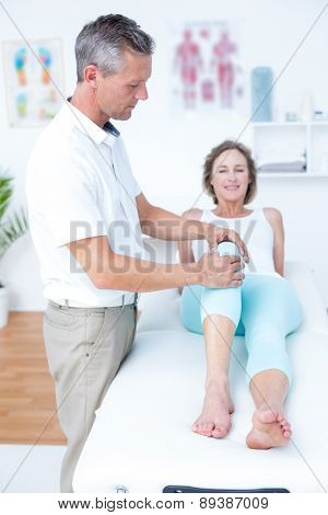 Physiotherapist examining his patients knee in medical ofice