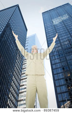 Excited delivery man with arms raised looking up against low angle view of skyscrapers