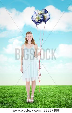 Happy hipster woman holding balloons against blue sky
