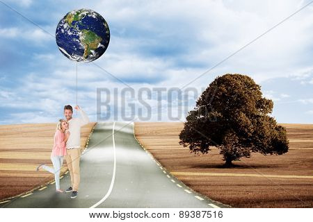 Attractive couple smiling and cheering against road leading out to the horizon