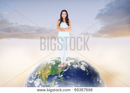 Pretty brunette smiling at camera against beautiful orange and blue sky