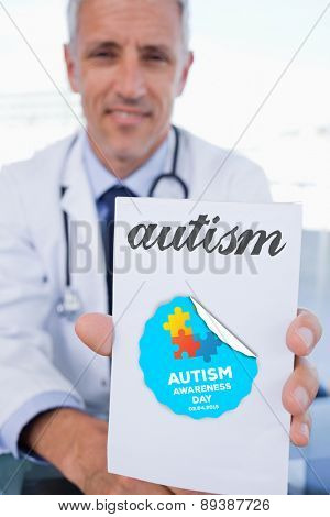 The word autism and portrait of a male doctor showing a blank prescription sheet against autism awareness day