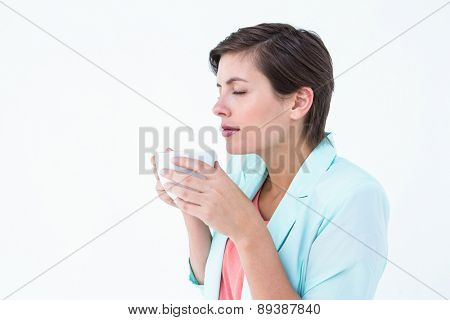 Peaceful woman drinking cup of coffee on white background
