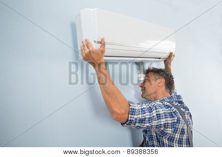 Male Technician Fixing Air Conditioner