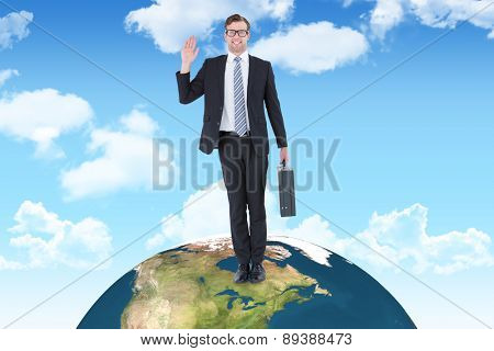 Geeky hipster businessman waving at camera against blue sky