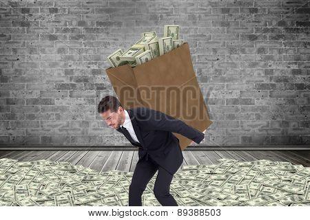 Businessman carrying bag of dollars against grey room
