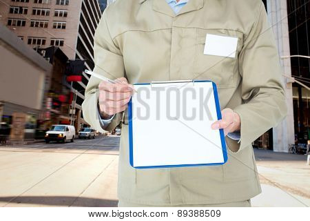 Delivery man showing blank paper on clipboard against new york street