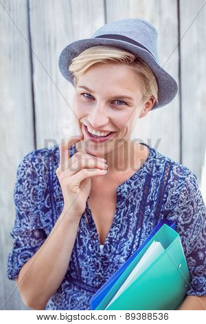Pretty blonde woman holding folders on wooden background