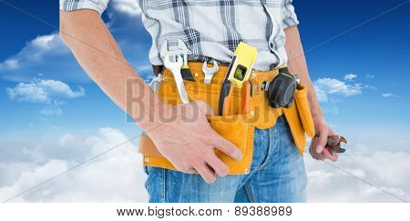 Cropped image of technician with tool belt around waist against bright blue sky with clouds