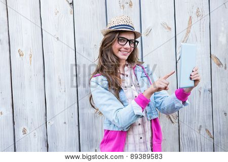 Pretty brunette using tablet pc against wooden planks