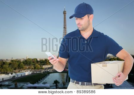 Delivery man using mobile phone while holding package against eiffel tower