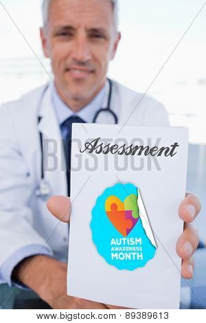The word assessment and portrait of a male doctor showing a blank prescription sheet against autism awareness month