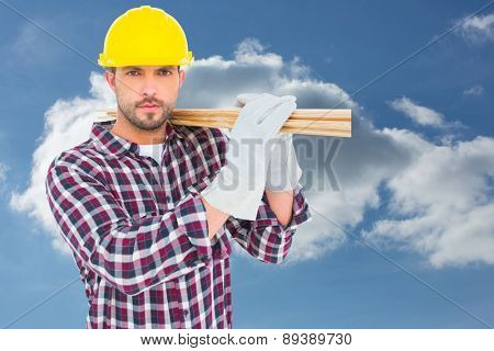 Handyman holding wood planks against cloudy sky