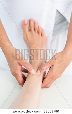Physiotherapist massaging her patients ankle in medical office