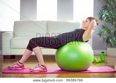 Fit woman doing sit ups on exercise ball at home in the living room