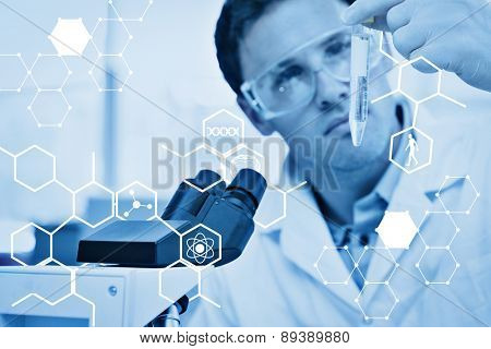 Science graphic against scientific researcher looking at test tube while using microscope in lab