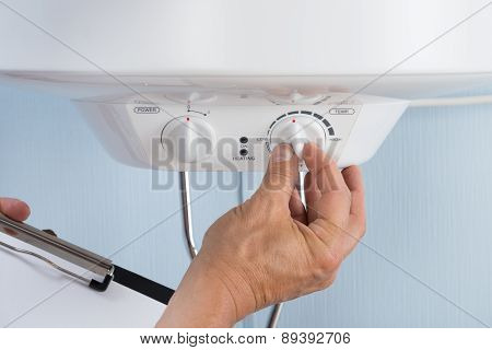 Person Adjusting Temperature Of Electric Boiler