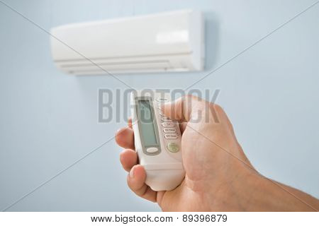 Man Adjusting Temperature Of Air Conditioner