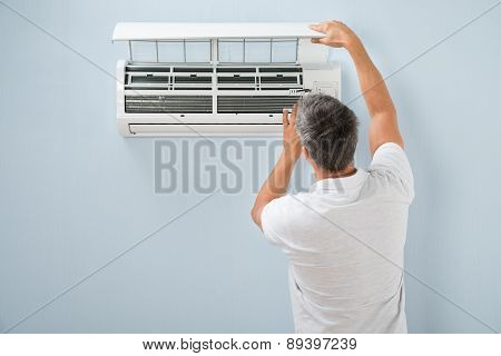 Man Cleaning Air Conditioning System