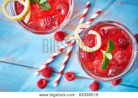 two colorful raspberry cocktails with mint and lemon shot from overhead