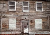 stock photo of abandoned house  - abandoned wooden house with boarded up windows - JPG