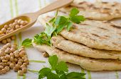 foto of pita  - Lebanese bread pita bread nice and fresh chickpeas in background simple cheap bread with herbs and garlic - JPG