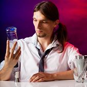 stock photo of bartender  - Young stylish man bartender preparing serving alcohol cocktail drink pouring vodka filling a jigger - JPG