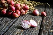pic of red shallot  - Shallot onions on old wooden table with shadow - JPG