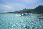 picture of camiguin  - small outrigger traditional fishing boat in the clear seas of camiguin island near mindanao in the philippines - JPG