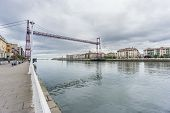 picture of suspension  - Wide view of the Bizkaia suspension bridge and promenade against cloudy sky in Portugalete - JPG