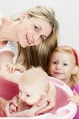 stock photo of bathing  - portrait of mother with her baby and daughter during bathing - JPG