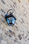picture of light fixture  - A classic black iron light fixture on a brick wall - JPG