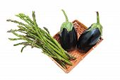 image of aubergines  - Brown basket with bunch of asparagus and two aubergines isolated on white background - JPG