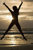 pic of stretching  - Sporty brunette stretching on the beach in the evening - JPG