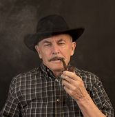 picture of hillbilly  - Cowboy in black hat with Pipe on a black background - JPG