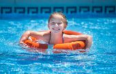 pic of lifeline  - happy little girl swims with a lifeline in the pool in  summer - JPG