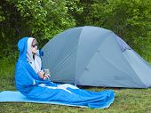pic of sleeping bag  - The man is resting in a sleeping bag on the background of tents and green forests - JPG
